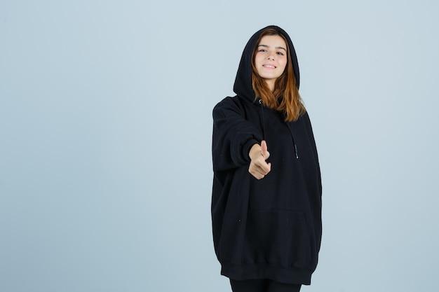 特大のパーカー、パンツに親指を立てて、うれしそうに見える若い女性。正面図。