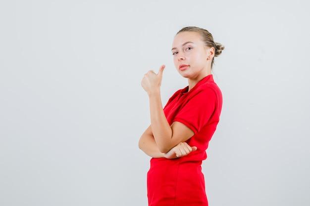 赤いtシャツに親指を立てて喜んでいる若い女性。