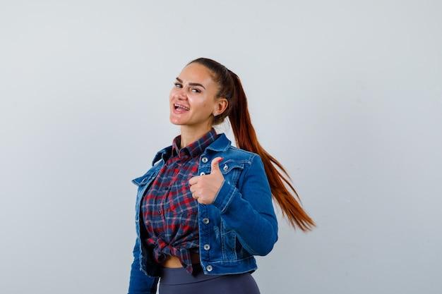 シャツ、ジャケットで親指を上げて陽気に見える若い女性、正面図。