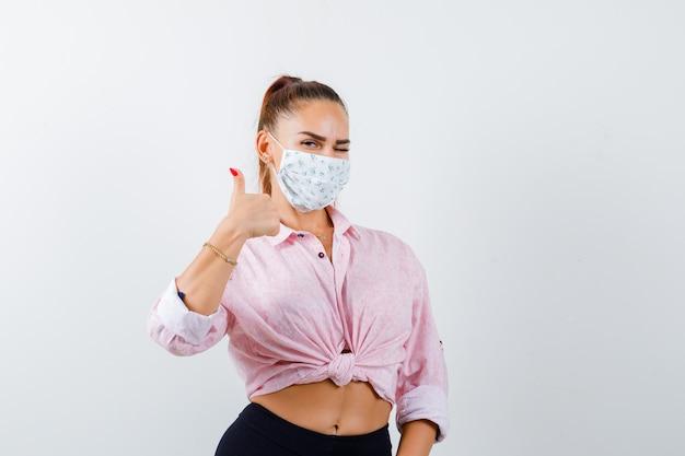 シャツ、ズボン、マスクで親指を表示し、陽気に見える若い女性