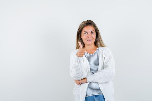 T- 셔츠, 재킷에 엄지 손가락을 표시 하 고 행복을 찾는 젊은 아가씨. 전면보기.