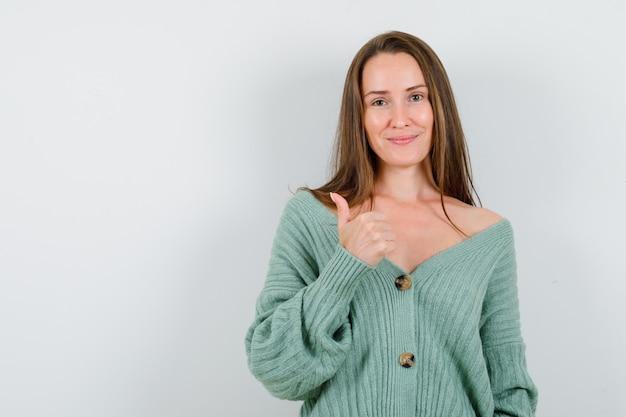 ウールのカーディガンで親指を立てて元気そうに見える若い女性。正面図。
