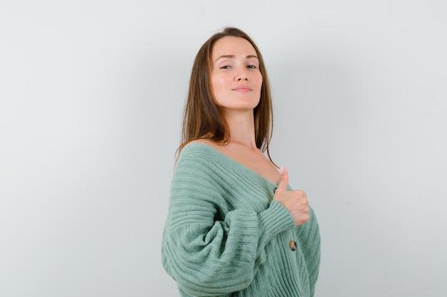 ウールのカーディガンで親指を表示し、誇らしげに見える若い女性、正面図。