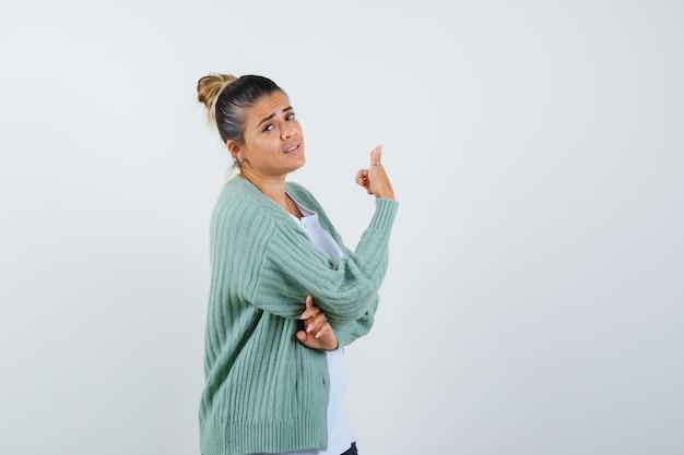 Giovane donna che mostra pollice in su in maglietta, giacca e sembra sicura