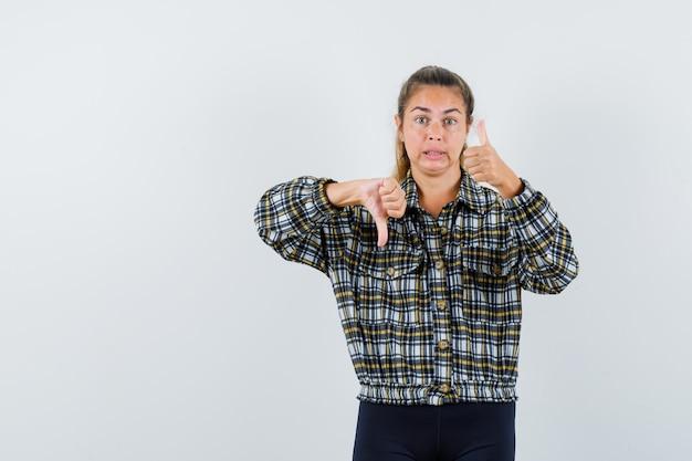 シャツ、ショートパンツで親指を上下に示し、混乱しているように見える若い女性、正面図。