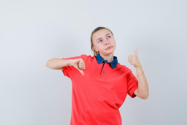 Tシャツで親指を上下に見せて躊躇しているお嬢様
