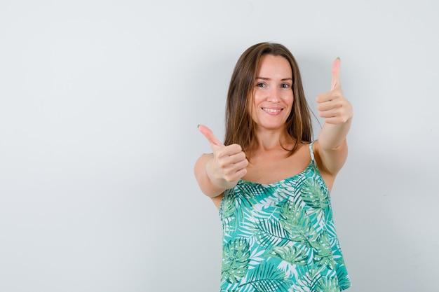 Giovane donna che mostra i pollici in camicetta e sembra felice. vista frontale.