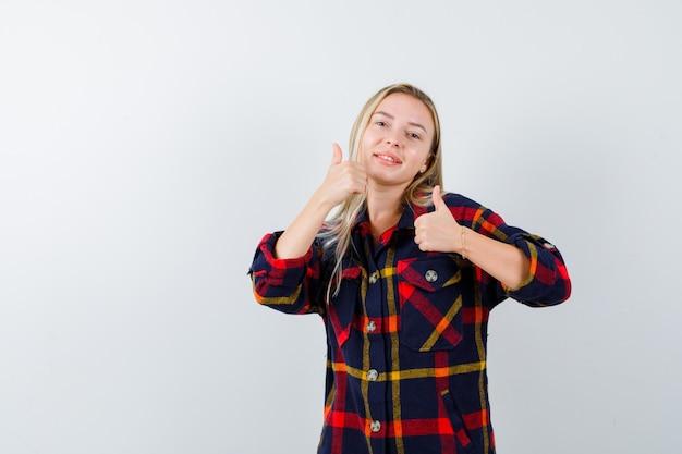 Giovane signora che mostra i pollici in su in camicia controllata e che sembra felice, vista frontale.