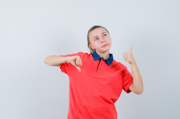 Young lady showing thumbs up and down in t-shirt and looking hesitant