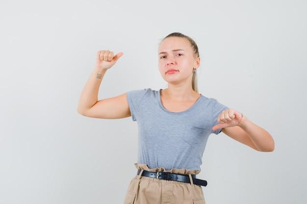Giovane signora che mostra i pollici su e giù in maglietta e pantaloni e sembra indeciso