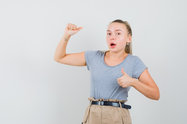 Young lady showing thumbs up and down in t-shirt and pants and looking surprised