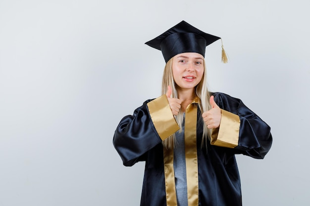 Молодая леди показывает палец вверх в академической одежде и выглядит уверенно.