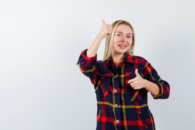 체크 셔츠에 엄지 손가락을 표시 하 고 활기찬 찾고 젊은 아가씨. 전면보기.