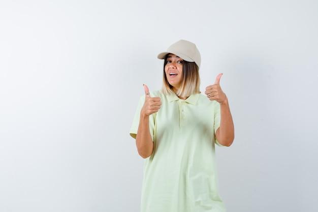 T- 셔츠, 모자에 엄지 손가락을 표시 하 고 긍정적 인 찾고 젊은 아가씨. 전면보기.