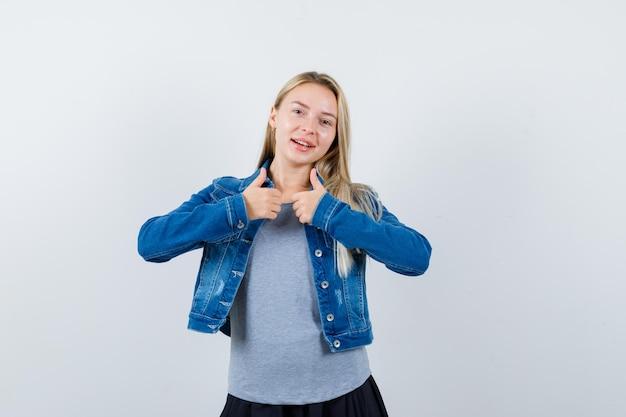 Молодая леди показывает палец вверх в футболке, джинсовой куртке, юбке и выглядит радостной.