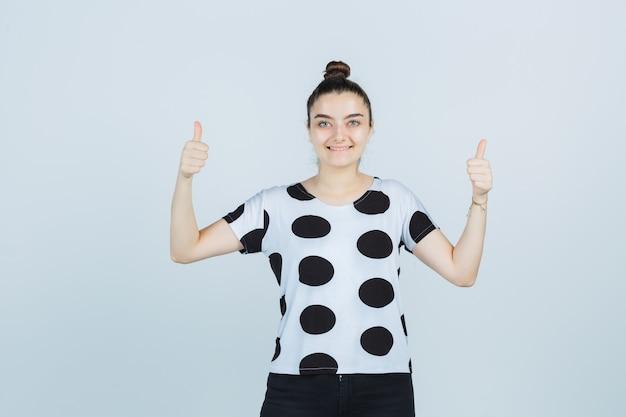 T- 셔츠, 청바지에 엄지 손가락을 표시 하 고 귀여운, 전면보기를 찾고 젊은 아가씨.