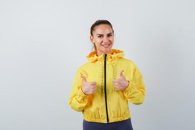 黄色いジャケットに親指を立てて楽観的に見える若い女性。正面図。
