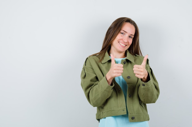 Young lady showing thumbs up in t-shirt, jacket and looking glad , front view.