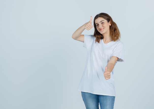 Giovane signora che mostra i pollici in su in maglietta, jeans e che sembra gioiosa, vista frontale.
