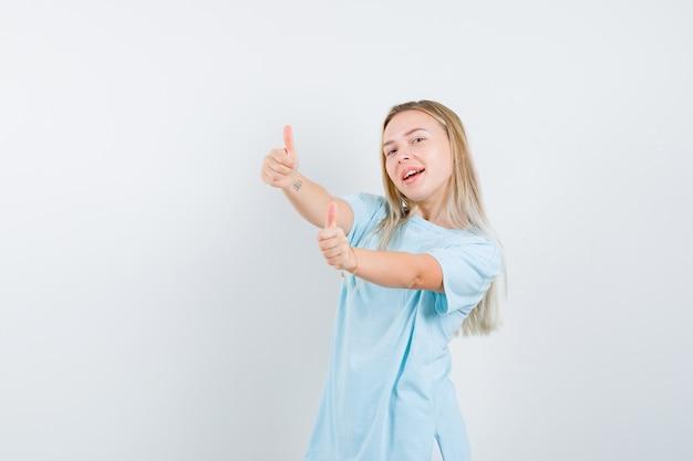Giovane signora che mostra i pollici in su in maglietta e che sembra felice, vista frontale.