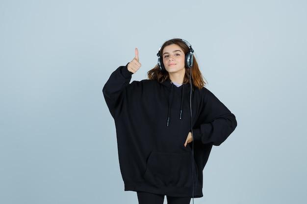 Юная леди показывает большие пальцы руки вверх, держа руку на талии в огромной толстовке с капюшоном, штанах и выглядит блаженно, вид спереди.