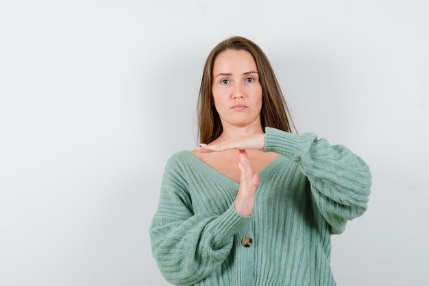 ウールのカーディガンでタイムブレイクジェスチャーを示し、真剣に見える若い女性。正面図。