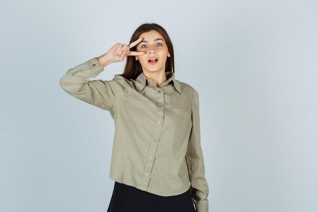 Молодая леди показывает v-знак возле глаза в рубашке, юбке и удивленно смотрит, вид спереди.