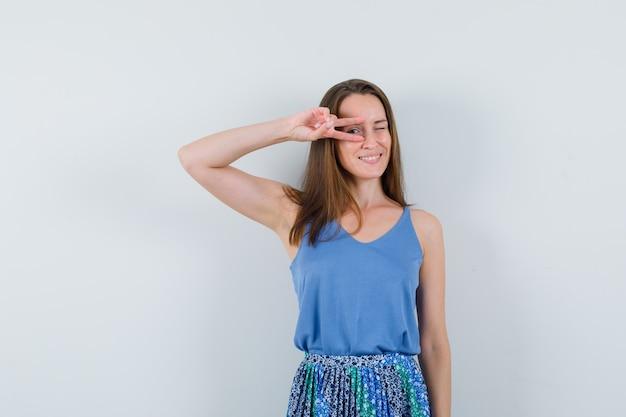 一重項、スカート、自信を持って目にvサインを示す若い女性