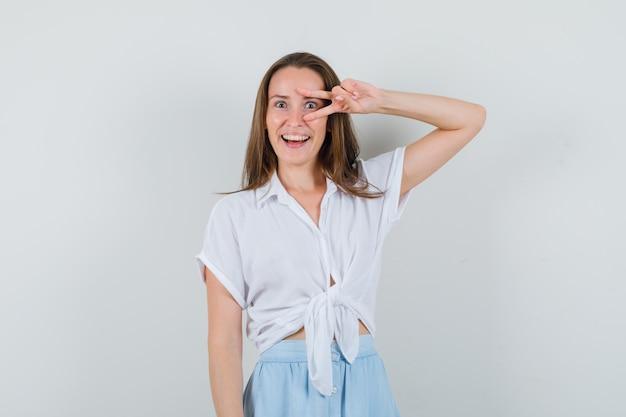 블라우스, 스커트에 그녀의 눈에 v 기호를 보여주는 젊은 아가씨