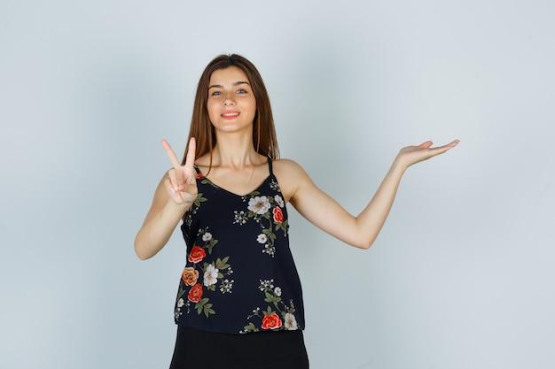 Молодая дама показывает знак v, разводит ладонь в блузке, юбке и выглядит весело, вид спереди.