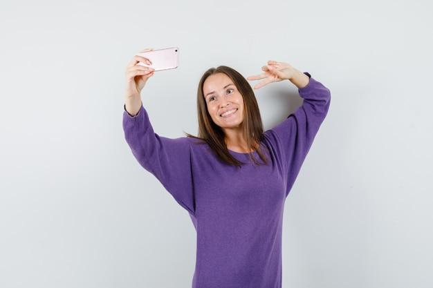 紫のシャツを着て自分撮りをしながら陽気に見えるvサインを示す若い女性。正面図。