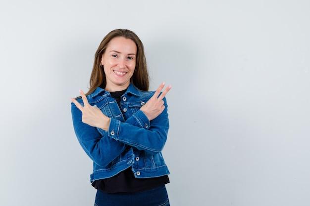 Giovane donna che mostra gesto di vittoria in camicetta, giacca e sembra sicura, vista frontale.