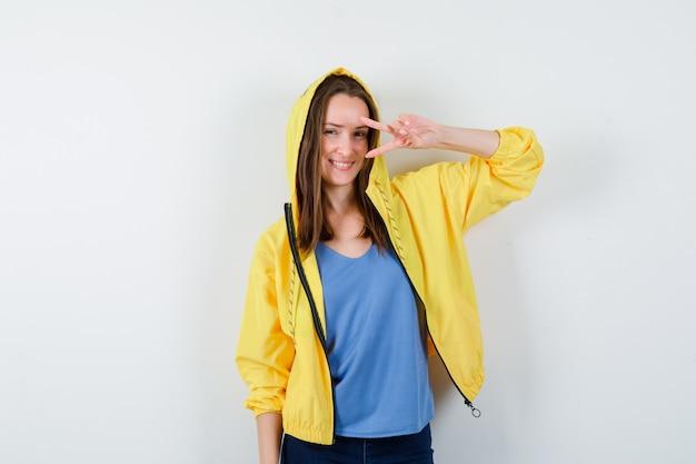 Giovane donna che mostra gesto di vittoria vicino all'occhio in t-shirt, giacca e guardando fiducioso, vista frontale.