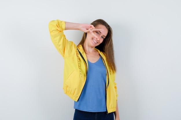 Tシャツで目に勝利のジェスチャーを示し、幸せそうに見える若い女性。正面図。