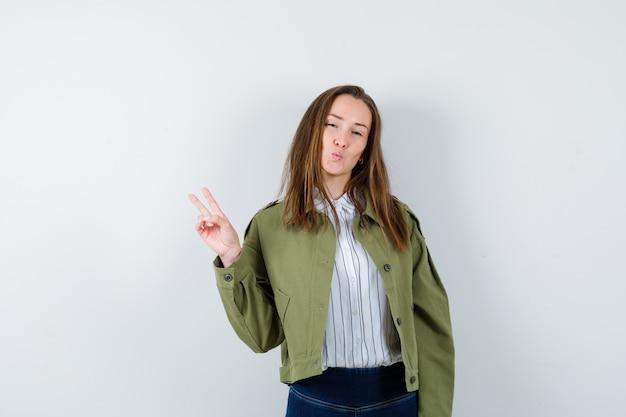 승리 제스처를 보여주는 젊은 아가씨, 셔츠, 재킷에 입술을 삐죽하고 자신감을 찾고. 전면보기.