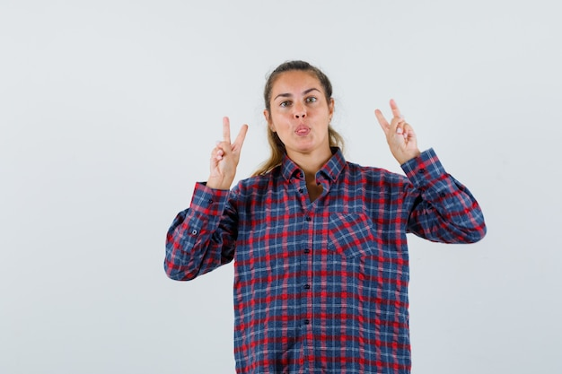 Giovane donna che mostra il gesto di vittoria, che attacca fuori la lingua in camicia a quadri e sembra sicura. vista frontale.