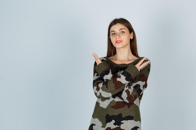Giovane donna che mostra il segno di vittoria, incrociando le braccia sul petto in maglione