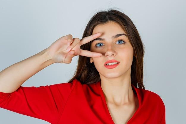 Giovane signora che mostra il segno di vittoria sull'occhio in camicetta rossa e sembra fortunata