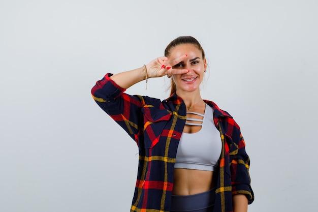 Giovane donna che mostra il segno della vittoria sull'occhio in cima, camicia a quadri e sembra allegra. vista frontale.