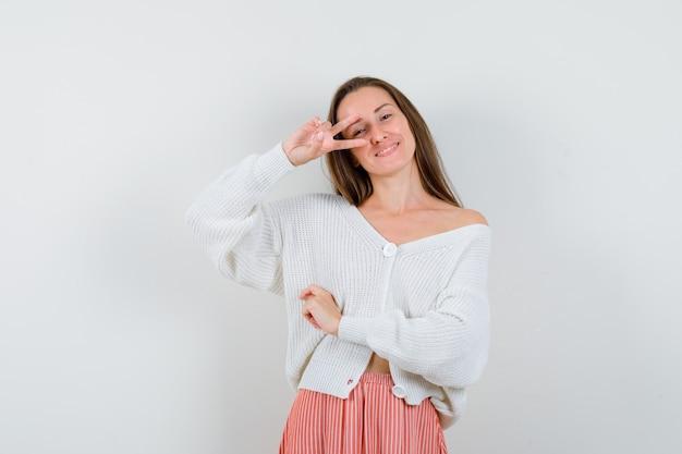 Молодая леди показывает знак победы в кардигане и юбке, выглядит блаженно изолированной