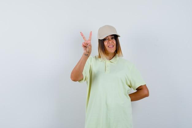 젊은 아가씨 t- 셔츠, 모자에 승리 기호를 표시 하 고 행복, 전면보기를 찾고.