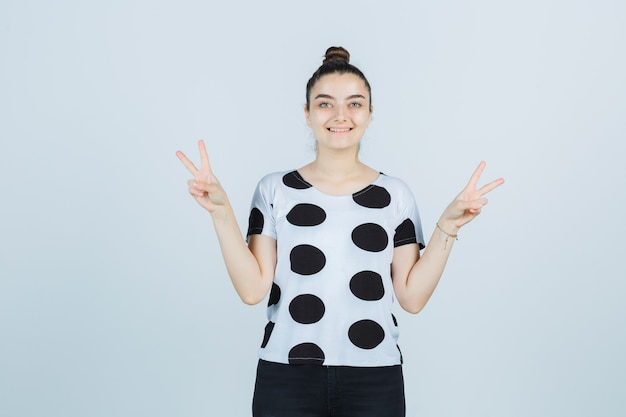 Tシャツ、ジーンズで勝利のサインを示し、幸運に見える若い女性。正面図。