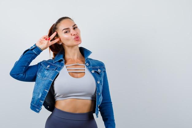 Giovane donna che mostra il segno della vittoria in alto, giacca di jeans e sembra attraente. vista frontale.
