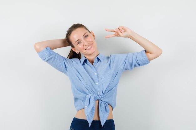 파란색 셔츠, 바지에 포즈를 취하고 즐거운 찾고있는 동안 승리 기호를 보여주는 젊은 아가씨.