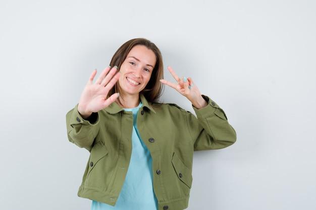 티셔츠, 재킷에 정지 제스처를 보여주고 행복해 보이는 동안 승리 기호를 보여주는 젊은 아가씨. 전면보기.
