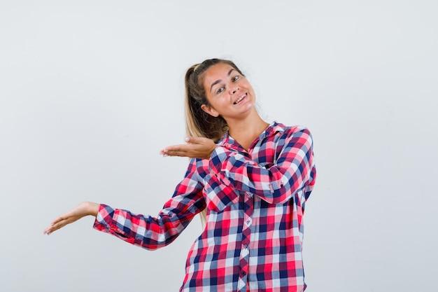Giovane signora che mostra gesto di benvenuto in camicia a quadri e sembra allegra. vista frontale.