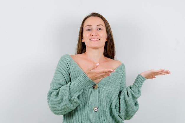 ウールのカーディガンで歓迎のジェスチャーを示し、自信を持って見える若い女性。正面図。