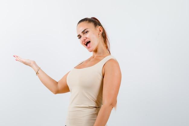 Giovane donna che mostra gesto di benvenuto in canottiera e guardando fiducioso, vista frontale.