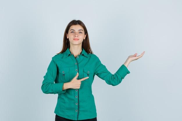緑のシャツを脇に向け、自信を持って見ている間、歓迎のジェスチャーを示す若い女性、正面図。