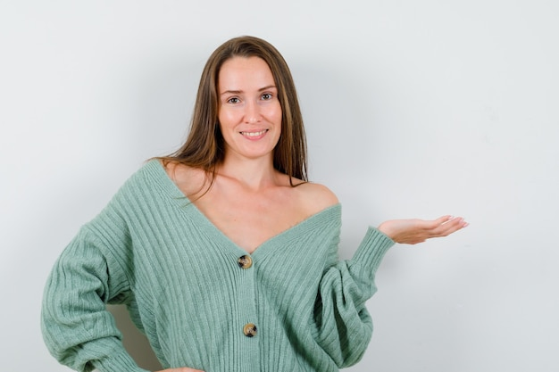 Giovane signora che mostra gesto di benvenuto in cardigan di lana e sembra allegra, vista frontale.